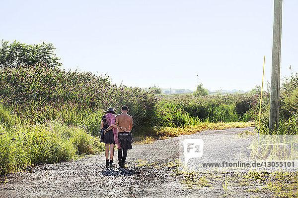 Rückansicht eines Paares mit umgebundenen Armen  das auf einer Schotterstraße durch ein Feld läuft