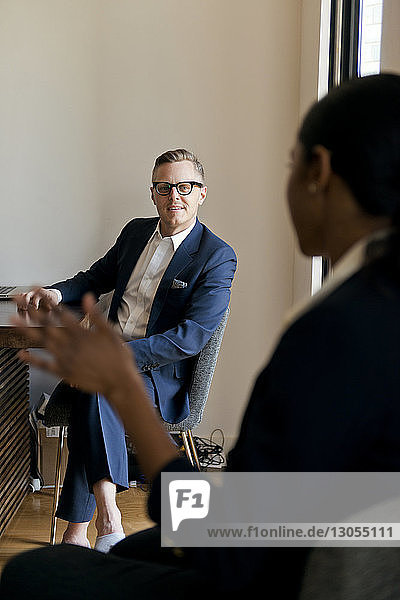 Businessman discussing with female colleague while sitting in office
