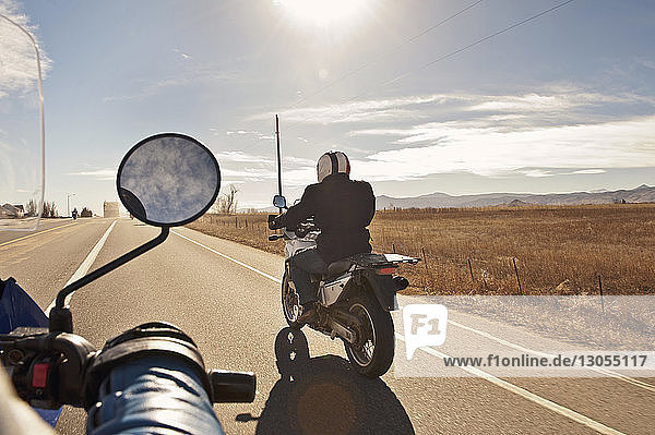 Cropped image of biker with friend riding on road against sky