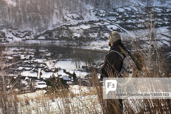 Wanderer mit Rucksack  der im Winter auf dem Berg steht