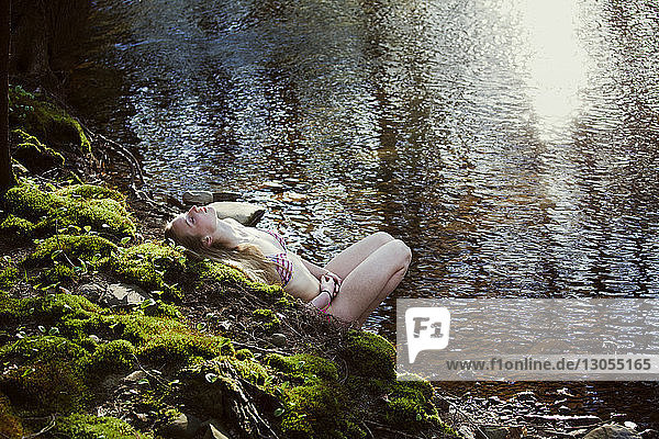 High angle view of woman relaxing at riverbank in forest