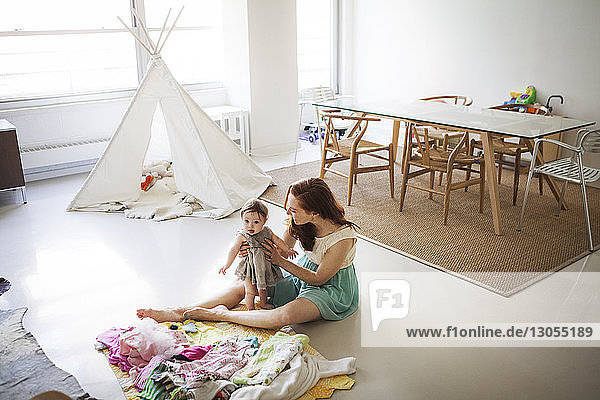 High angle view of mother sitting with baby girl in living room
