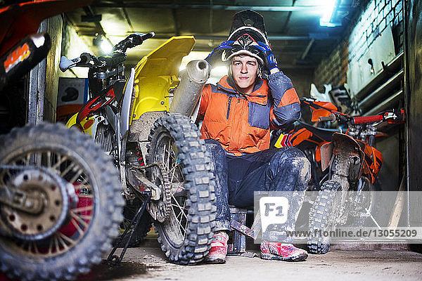 Portrait of male biker holding helmet and sitting in garage