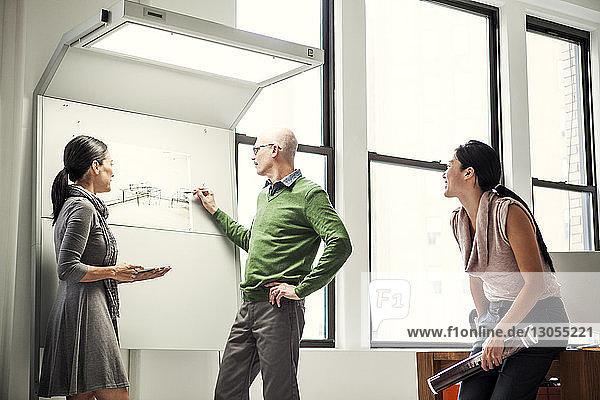 Geschäftsmann skizziert Diagramm an Bord  während er seinen Kollegen im Büro zur Seite steht