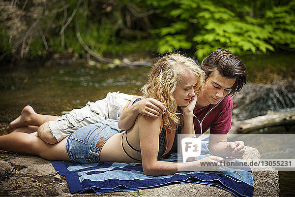 Couple listening music through mobile phone while lying on riverbank