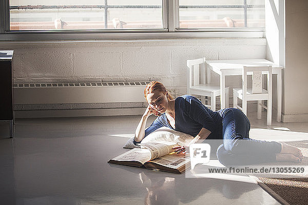Woman reading book while lying on floor at home