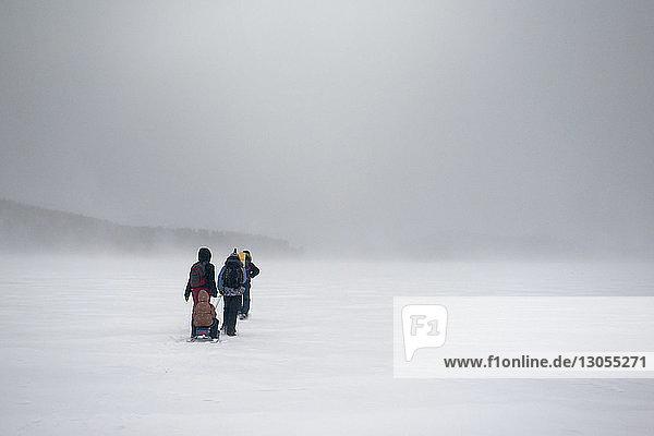 Rückansicht von Menschen  die auf einem schneebedeckten Feld gehen