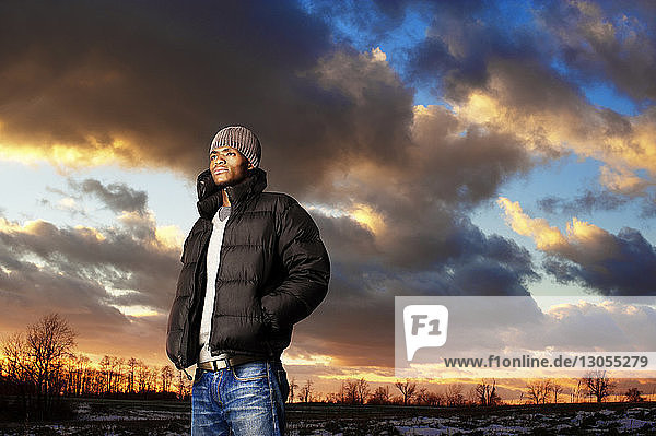 Thoughtful man standing against cloudy sky during sunset