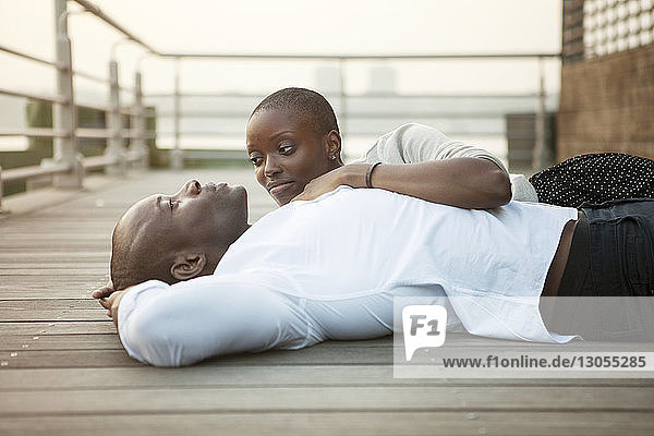 Couple lying on floorboard at pier
