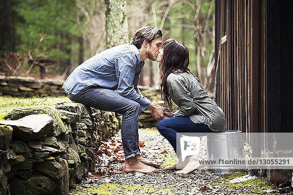 Seitenansicht eines Paares  das sich auf den Mund küsst  während es an einer Hütte sitzt