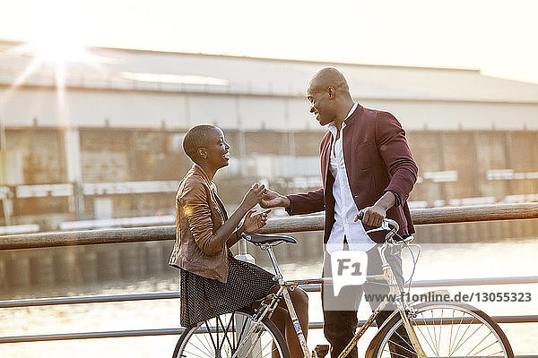 Man giving flower to woman sitting on bicycle