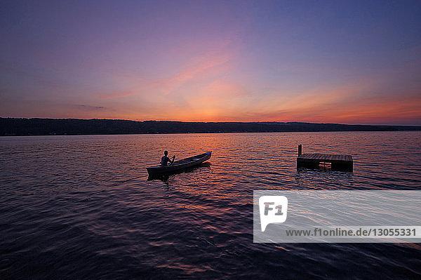 Mann rudert Boot auf See gegen den Himmel bei Sonnenuntergang