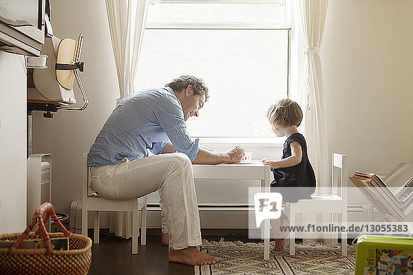 Side view of father teaching daughter coloring at table in home