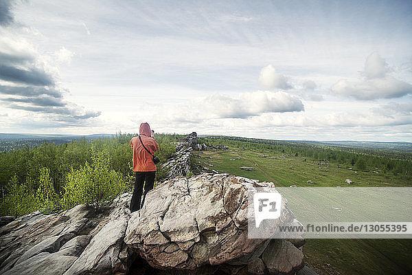 Rückansicht einer Frau  die auf einer Felsformation gegen den Himmel steht