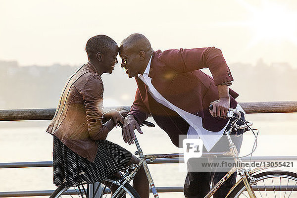 Romantic couple with bicycle by railing at pier