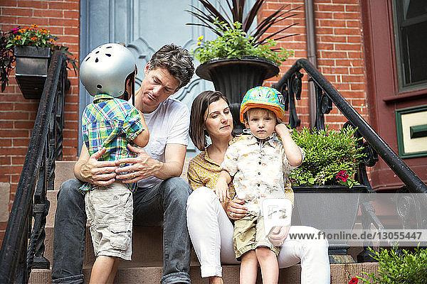 Family sitting on steps outside house