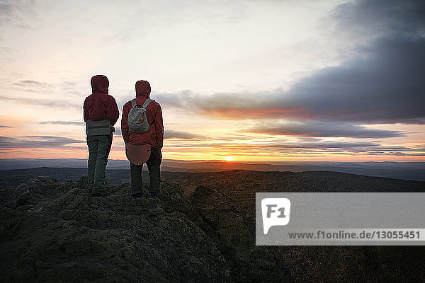 Hikers standing on rocks at mountain against sky