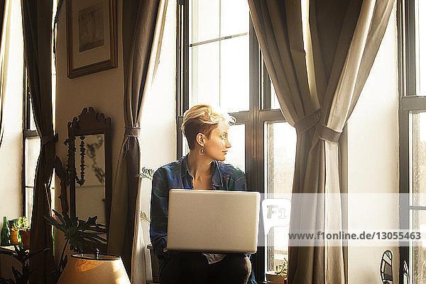 Frau mit Laptop-Computer sitzt zu Hause auf der Fensterbank