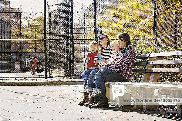 Familie sitzt auf Bank im Park
