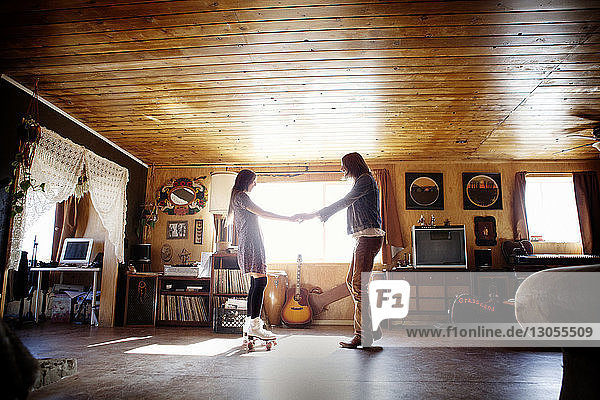 Side view of couple holding hands while standing at home