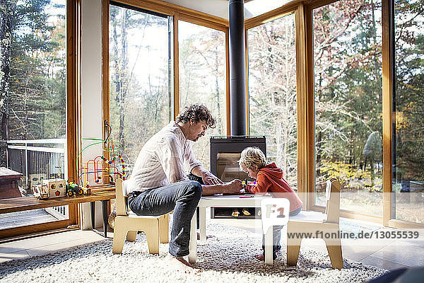 Vater bringt Sohn das Schreiben bei  während er zu Hause am Stuhl sitzt