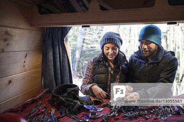 Ehepaar betrachtet Kletterausrüstung  während es beim Wohnmobil steht