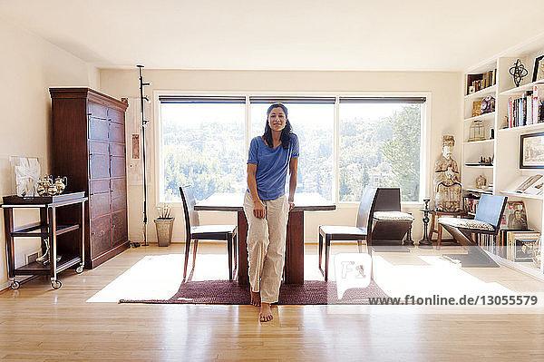 Lächelnde Frau steht zu Hause am Tisch