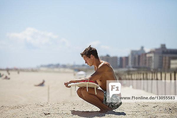 Mann sieht Surfbrett an,  während er auf Sand gegen den Himmel kauert