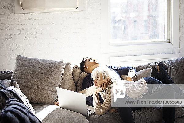 Woman using laptop while lying on man sitting on sofa at home