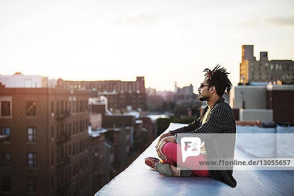 Seitenansicht eines Mannes  der auf einer Stützmauer auf einer Terrasse sitzt