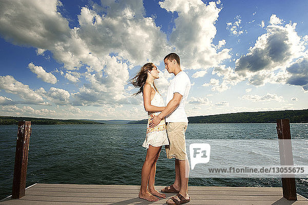 Side view of young couple looking at each other while standing on jetty over lake against sky