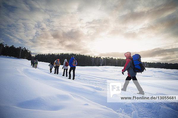 Freunde wandern auf schneebedecktem Feld gegen wolkigen Himmel