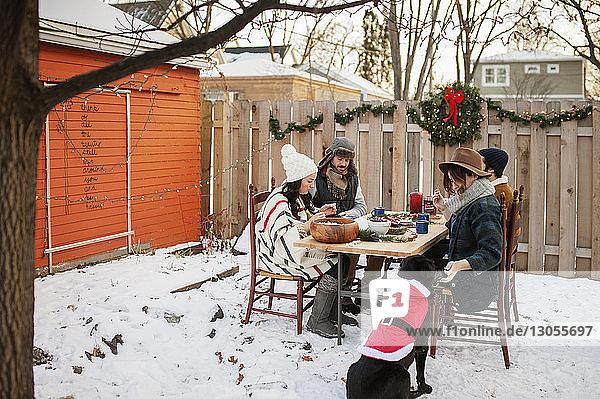 Freunde genießen bei Tisch und im schneebedeckten Hinterhof