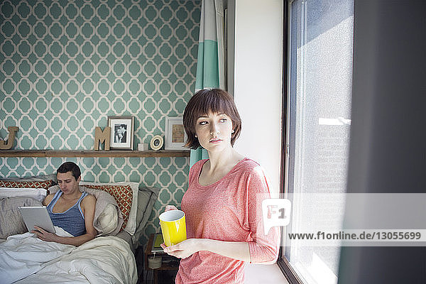 Thoughtful woman holding coffee cup while man using tablet computer in bedroom
