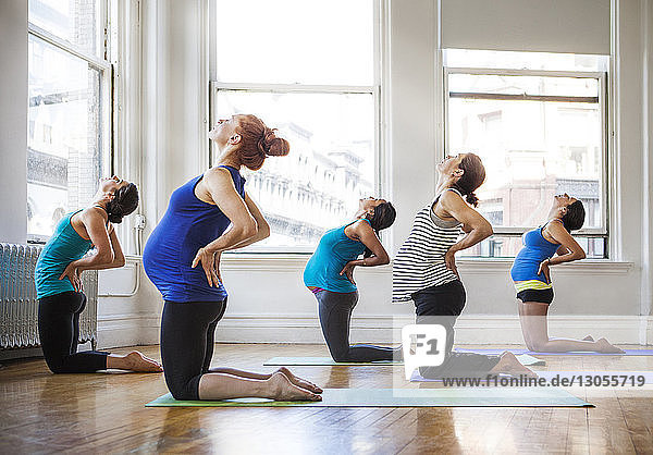 Pregnant women practicing yoga in gym