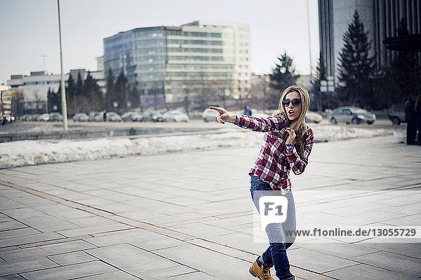 Junge Frau zeigt stehend auf Bürgersteig in der Stadt