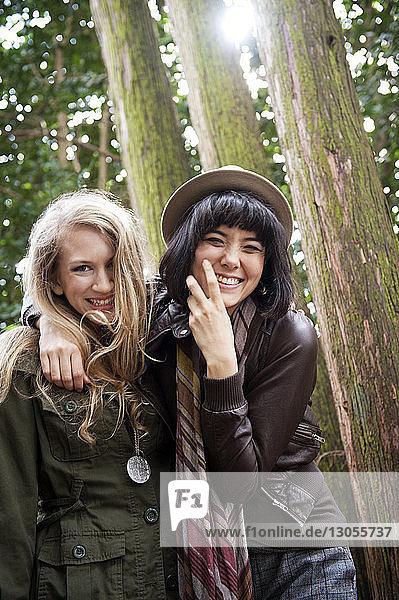 Porträt einer glücklichen Freundin im Wald stehend
