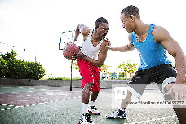 Sportsmen playing basketball in court