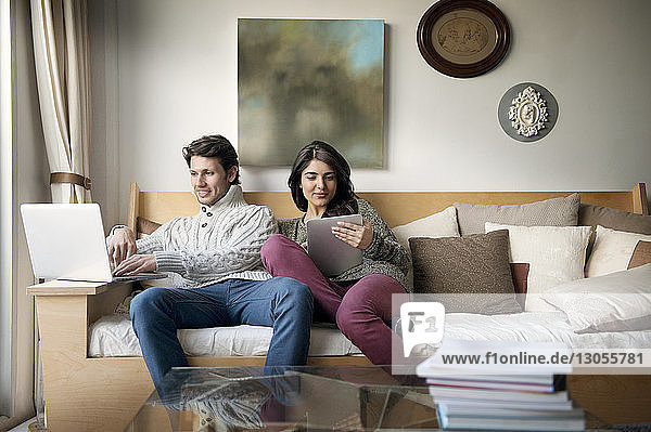 Young couple using technologies on sofa at home