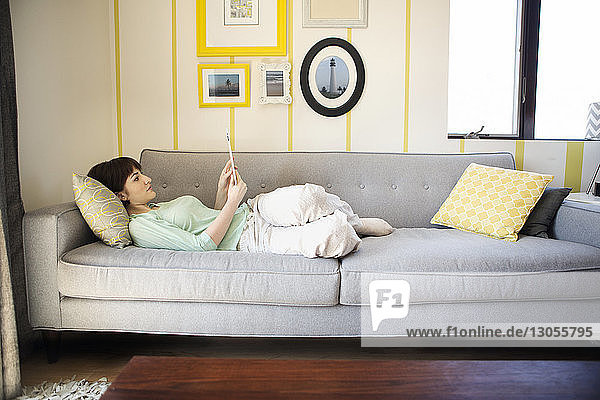 Woman using tablet computer while lying on sofa at home