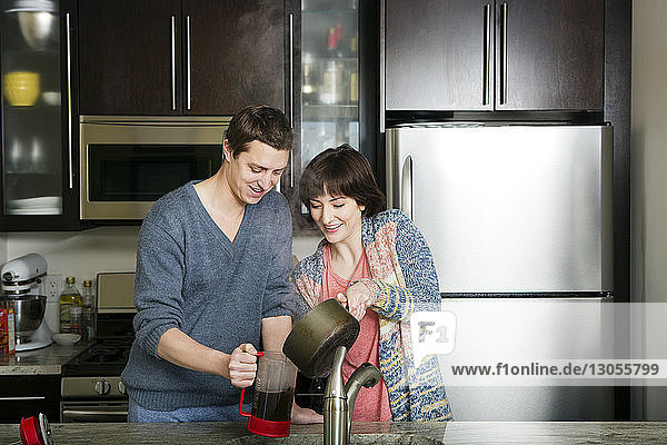 Man and woman preparing coffee in kitchen at home