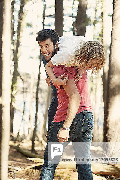Portrait of happy man carrying woman in forest