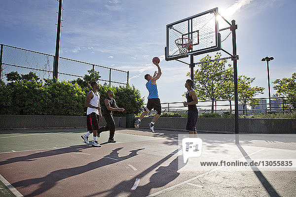 Friends playing basketball in court on sunny day