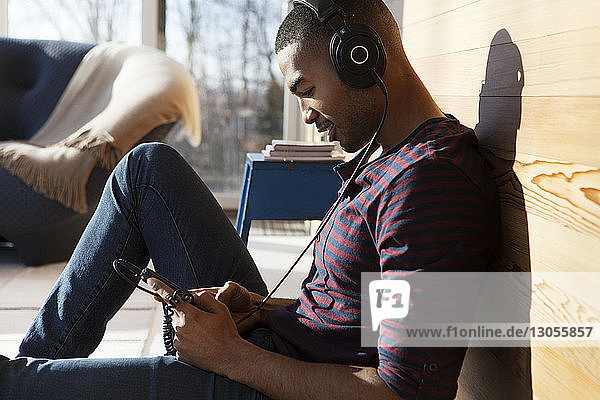Man using smart phone while listening music on headphone at home