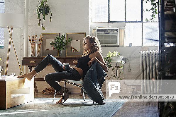 Seitenansicht einer nachdenklichen Frau  die zu Hause auf einem Stuhl sitzt