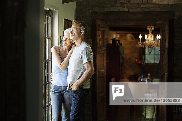 Senior couple looking through window while standing at home