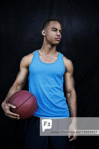 Confident sportsman holding basketball while looking away against black wall
