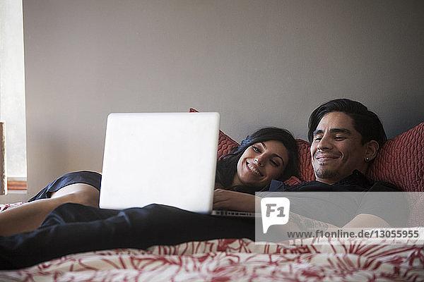 Lächelndes Paar benutzt Laptop-Computer  während es zu Hause im Bett liegt