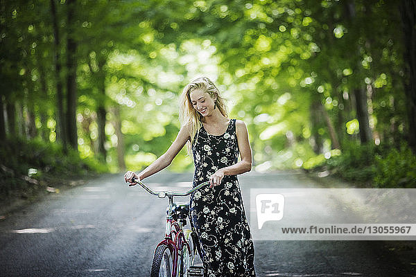 Smiling woman with bicycle walking on road