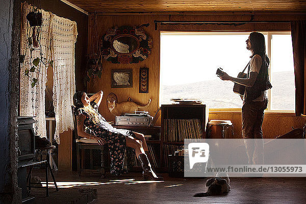 Man playing guitar while woman relaxing on chair at home